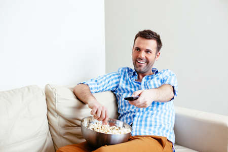 Young smiling man changing channels with a remote control
