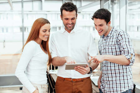 Portrait of three smiling professionals looking at a tablet Stock Photo