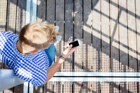 Birds eye photo of a blong man writing a message on his mobile Stock Photo