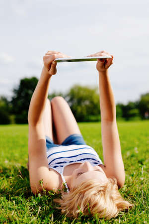 Photo of a woman lying on her back on the grass and using a tablet Stock Photo