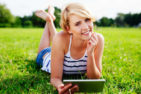 Portrait of a pretty woman lying on the grass with a digital tablet in her hand