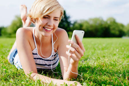 Young pretty woman lying on the grass in the park and listening to mp3s