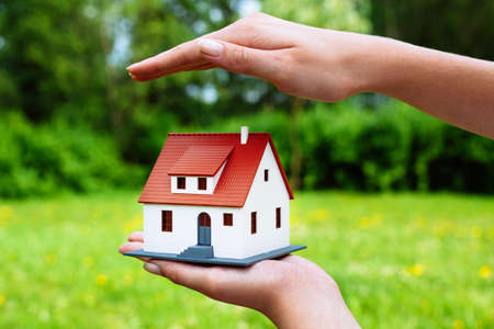 Home insurance concept.Photo of a hand hovering over a miniature house 스톡 콘텐츠