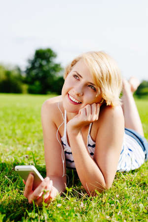 Young happy woman listening to music and enjoying her day in the green