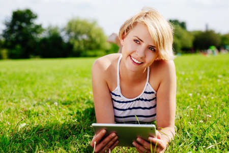 Portrait of a blond woman lying on the grass and holding a tablet Stock Photo