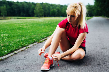 Photo of a female jogger sitting on the ground and lacing up her running shoes