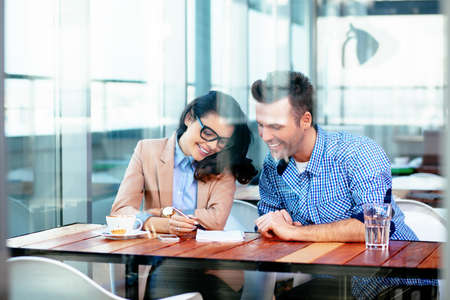Smiling couple sitting at a table and taking notes