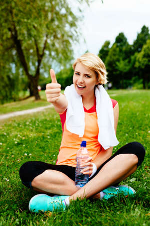 Photo of a satisfied woman runner sitting on the grass after a park run