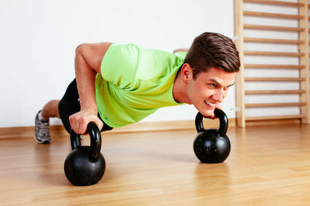 Sportsman sculpting his body with kettlebell Stock Photo