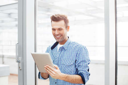 Young man standing next to w window and  having fun with a tablet