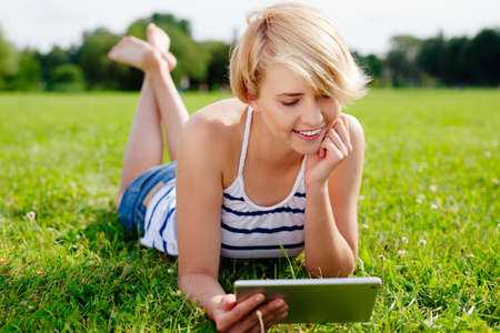 Photo of a blond woman surfing the web on her tablet and lying on the grass Stock Photo