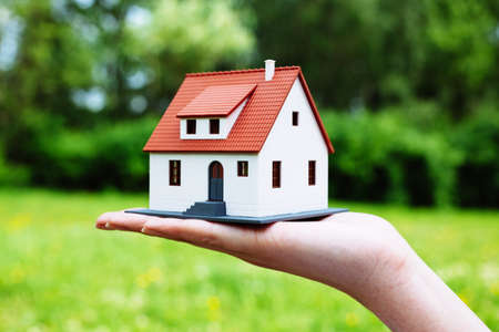 Photo of a miniature house held by a person