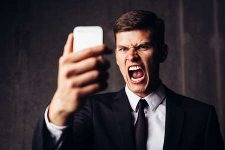 Angry businessman yelling after having read an sms