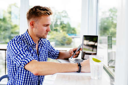 Young handsome man holding a smartphone and reading texts Stock Photo