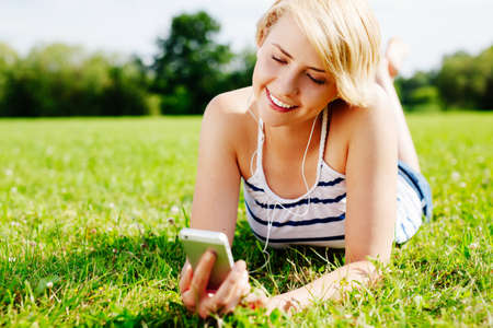 Photo of young attractive woman with earphones lying on the grass Stock Photo