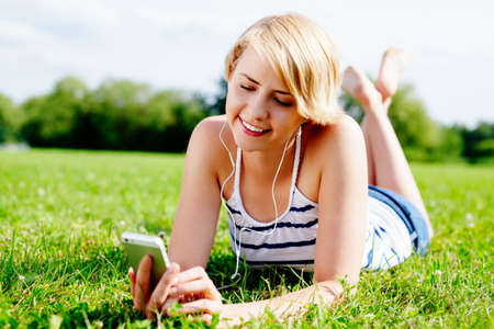 Young smiling woman listetning to music and relaxing on the grass