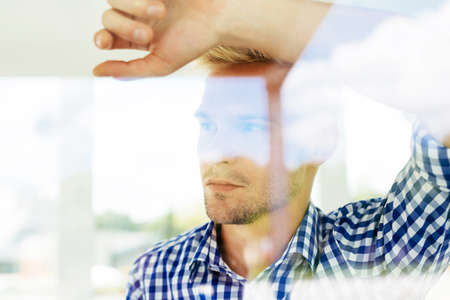Portrait of a handsome thoughtful man looking through a window