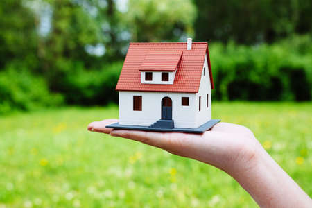 Photo of a miniature house against a green backdrop Stock Photo