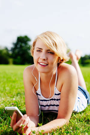 Portrait of a young woman listening to mp3s and lying on the grass