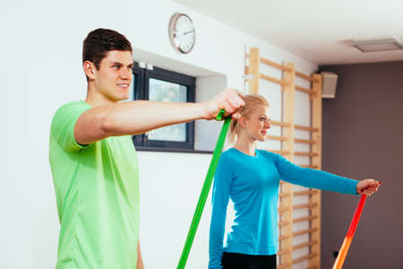 Smiling young people exercising with isometric bands