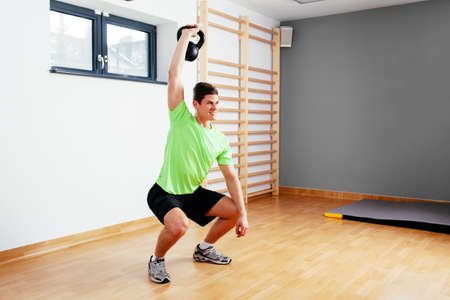 Happy athletic man exercising with kettlebell
