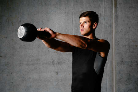 Photo of a sportsman exercising with a weight Foto de archivo