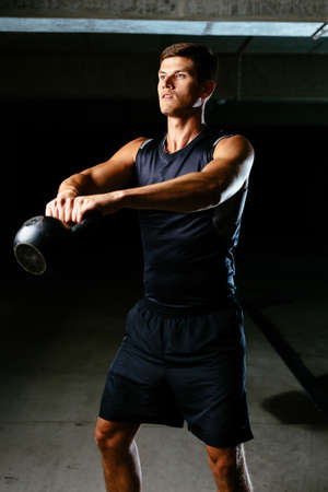 Muscular athlete toning his muscles with a kettlebell Stock Photo