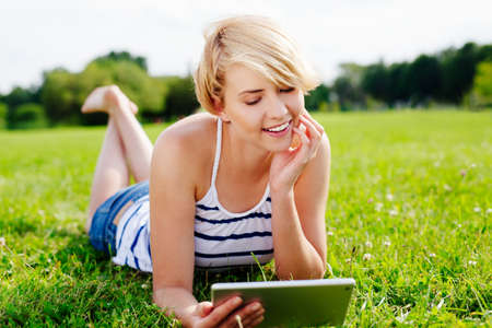 Photo of a pretty woman lying in the park and browsing the web on her tablet