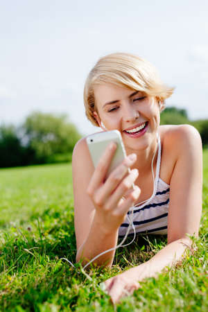 Portrait of an attractive blond woman with earphones lying on the grass Stock Photo