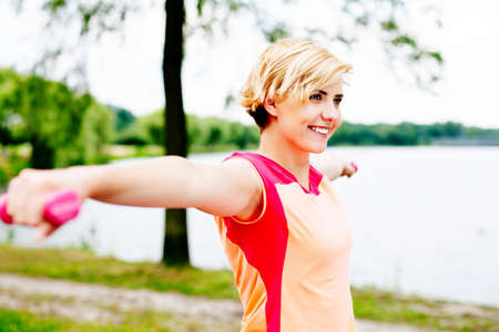 Photo of a blond woman lifting weights in the park