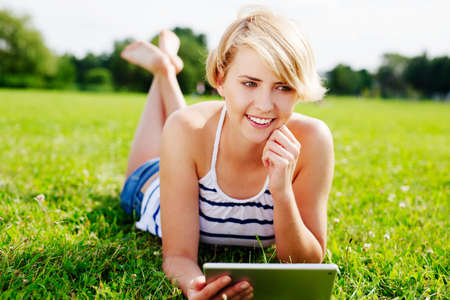 Portrait of a young woman using a tablet and lying on the grass