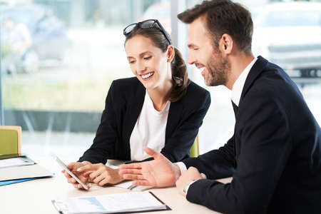Two colleagues working together with smartphone and business documents