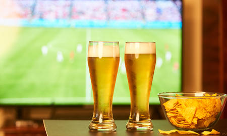 Two glasses of beer in front of TV playing football