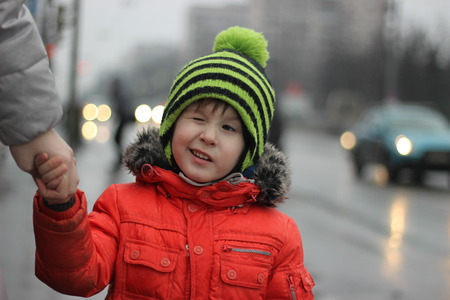 dowdy: Boy winks in the hat with bubo. Little boy wear warm red cat with fur and winks making grimace