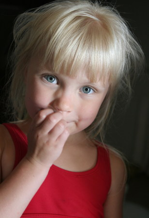 Little girl shy and put hand in the mouth. She has blonde hairs and blue eyes Archivio Fotografico