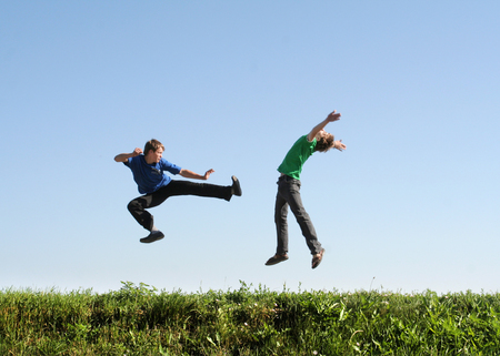 Fight in jump. Two men make sport by fighting in the air Stock Photo