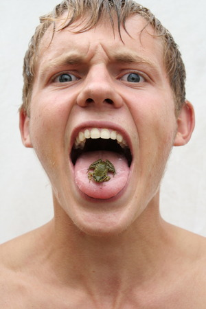 timidity: Delicacy frog on the tongue in mouth of man. Man is going to eat alive frog and frightened of it Stock Photo