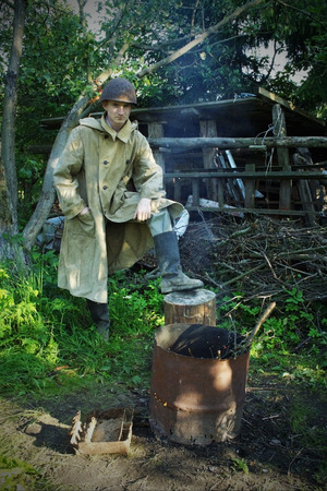 World War Two Soldier in helmet and cloak stand on stump with rubber boot as a winner Stock Photo