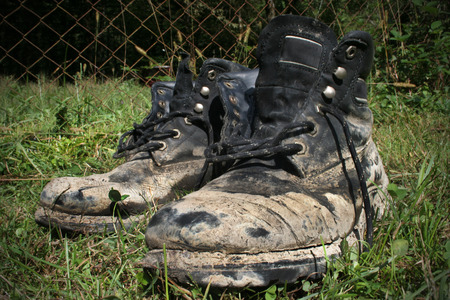 muddy clothes: Dirty boots after hard hiking dry on sun in grass. Stock Photo