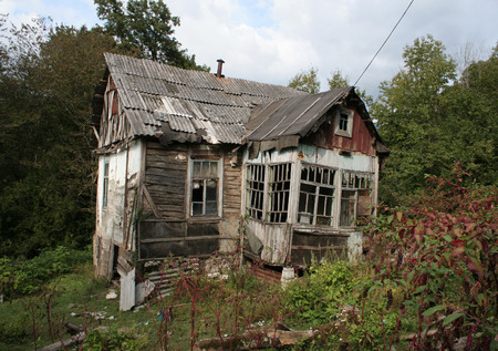 Terrible house with ghosts for horror stories. Almost destroyed big hut in forest. Stock Photo