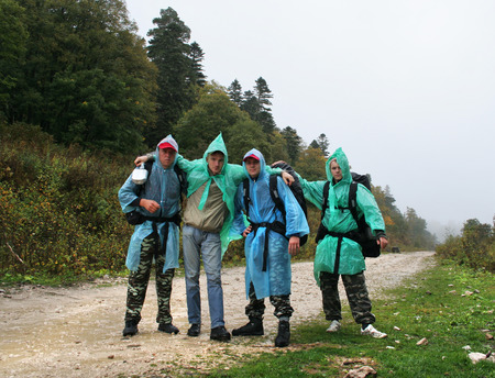 anorak: Four friends embrace as strong team on the road in mountains. Travelers are ready for adventures Stock Photo