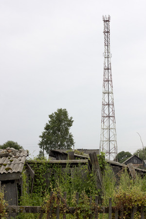 reaches: Communications tower in remote village among old poor houses. Internet reaches remote places.
