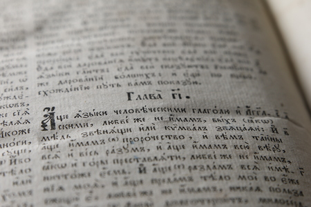 Open book with light spotlight on text. Reading of opened book educate reader. Ancient Bible text reading on black background. Russian bible