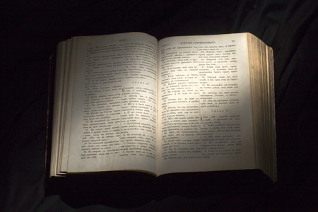 reader: Open book with light spotlight on text. Reading of opened book educate reader. Ancient Bible text reading on black background. Russian bible