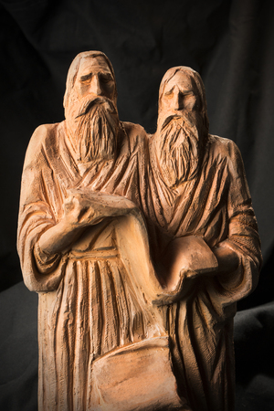 Slavonic educators Cyril and Methodius clay statues close up image. Old men hold scroll of holy scriptures. Russian alphabet makers