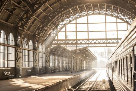 Alba dell'interno di tramonto della stazione ferroviaria nella seppia. Carrello e piattaforma con tetto di costruzione. Viaggiare in treno sulla ferrovia