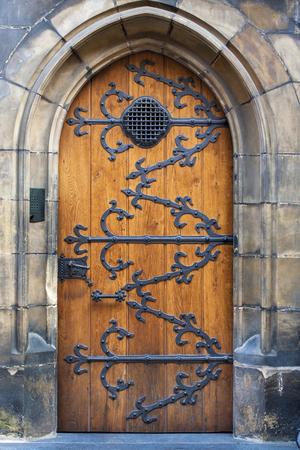 door handle: Medieval door with metal decoration. Wooden old door closed