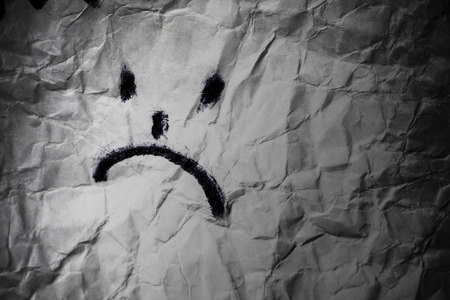 Dissapointed smile. Sad face on crumpled paper in dark background. Depression treatement concept