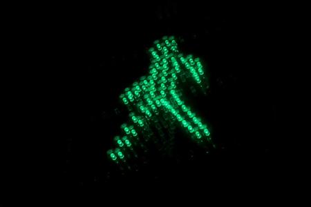 Verde signo de luz de pie peatonal. Pie verde en bacgkround negro. Semáforo de tráfico de cerca Foto de archivo - 86581264