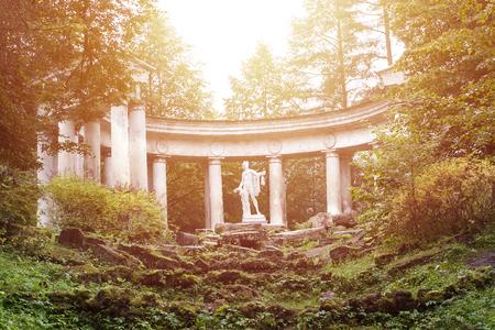 Ancienne statue grecque d'Appolo parmi les piliers détruits et les ruines dans l'ancien parc européen de Saint-Pétersbourg, Pavlovsk Banque d'images - 89130015